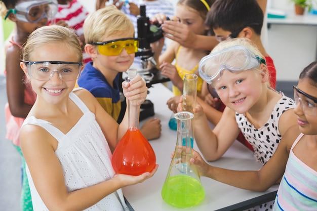 Porträt von kindern, die laborflasche im labor halten