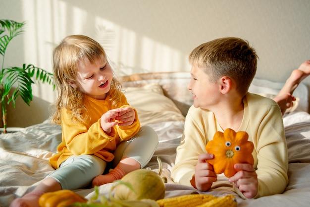 Porträt von kindern, die mit kürbissen spielen
