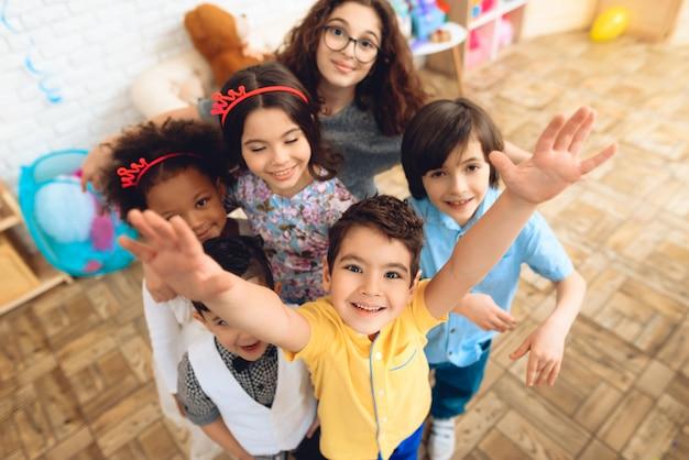 Porträt von kindern in den feiertagshüten an der geburtstagsfeier.