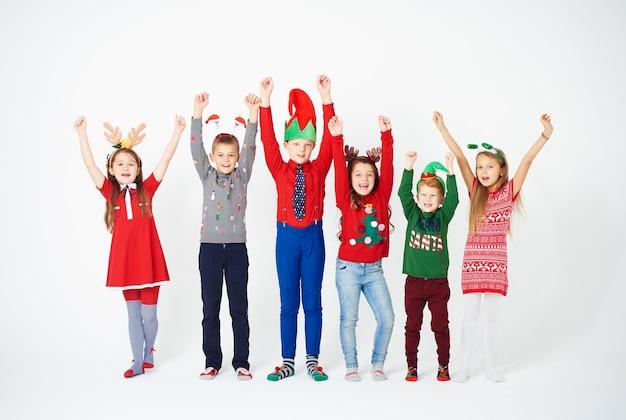 Porträt von kindern in voller länge mit erhobenen händen