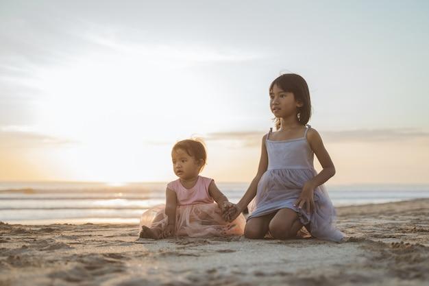 Porträt von kleinen schwestern, die einen urlaub am strand genießen