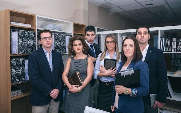 Porträt von kollegen im büro, die für ein meeting in der zentrale bereit stehen