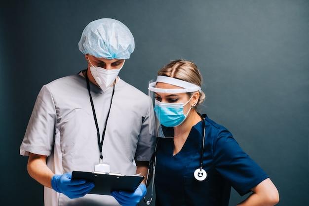 Porträt von krankenhausmitarbeitern pflegt kollegen in medizinischen schutzmasken, die auf dunklem hintergrund lokalisiert werden.