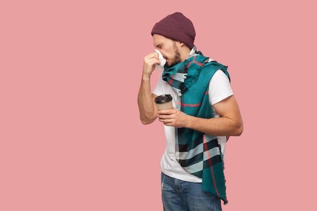 Porträt von krankheit moderner bärtiger junger hipster-mann in weißem hemd und lässigem hut, niesen der serviette, heißes getränk in pappbecher haltend. innen, isoliert, studioaufnahme, rosa hintergrund