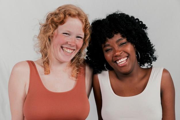 Porträt von lächelnden afrikanischen und blonden jungen frauen gegen grauen hintergrund