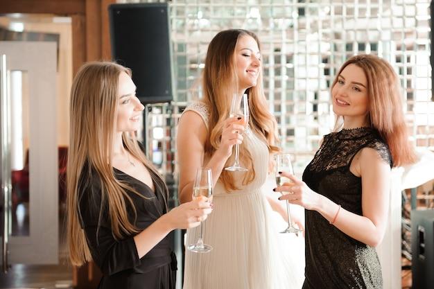 Porträt von lächelnden freunden, die glas champagner halten, während an der bar tanzen.