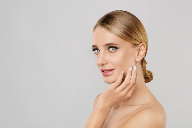 Porträt von lächelnden schönen blondinen mit natürlichem bilden das berühren ihres gesichtes.