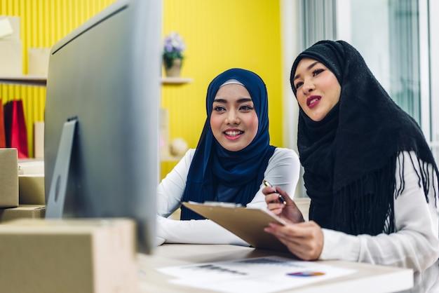 Porträt von lächelnden schönen muslimischen besitzern, die an laptop-computer mit paketboxen auf tisch zu hause arbeiten