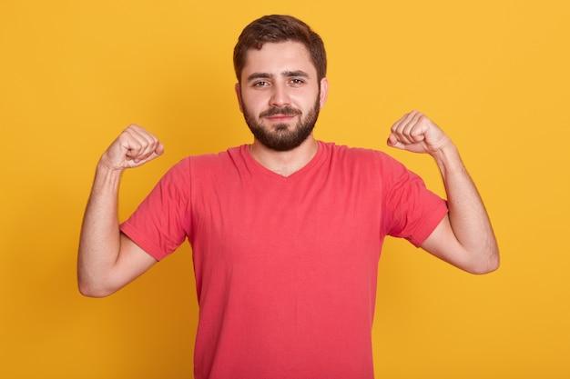 Porträt von lächelnden starken bärtigen männern kleidet lässiges rotes t-shirt, das bizeps zeigt