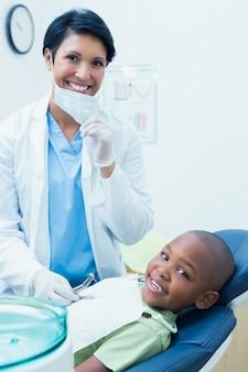 Porträt von lächelnden untersuchungszähnenzähnen des weiblichen zahnarztes