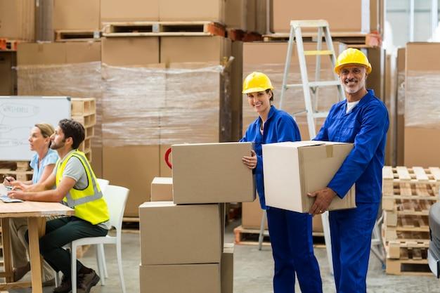 Porträt von lieferarbeitern, die pappkarton tragen