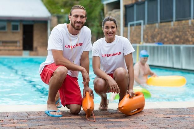 Porträt von männlichen und weiblichen rettungsschwimmern, die rettungsdosen am pool halten