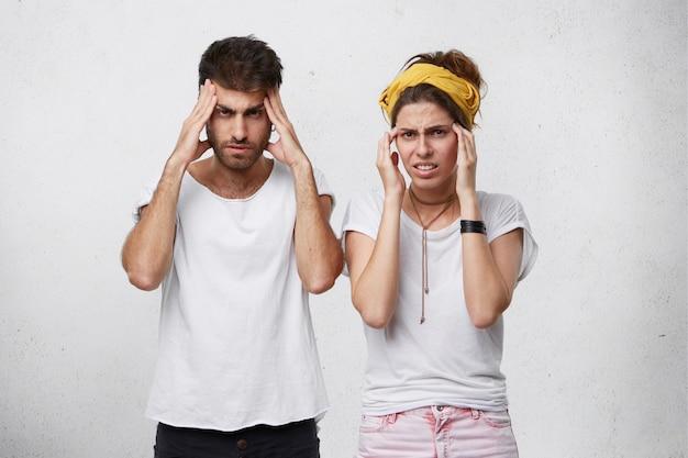 Porträt von mann und frau mit konzentrierten und verwirrten blicken, während sie versuchen, sich an etwas zu erinnern, das ihre hände an den schläfen hält
