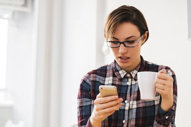 Porträt von mitteilungen eines entsetzten mädchenlesens auf smartphone