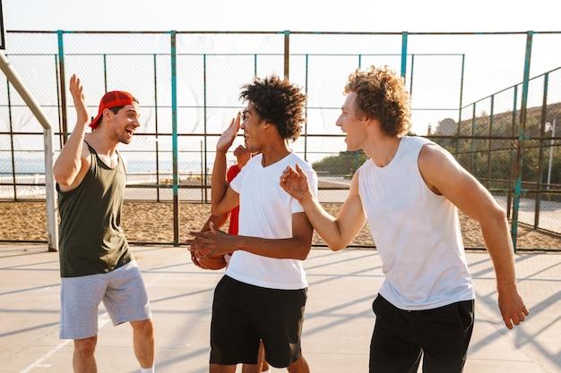 Porträt von multiethnischen sportlichen männern, die basketball am spielplatz im freien, während des sonnigen sommertages spielen