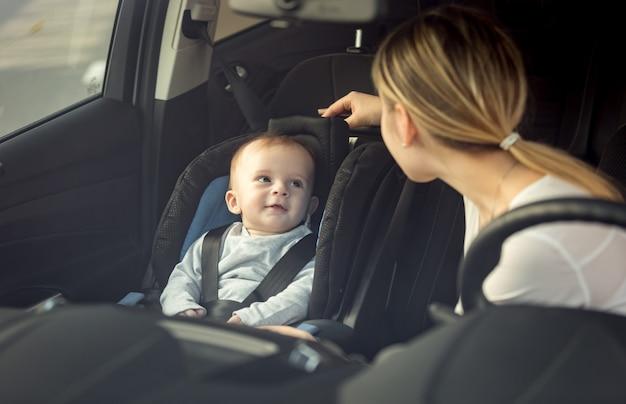 Porträt von mutter und baby, die im auto auf den vordersitzen sitzen