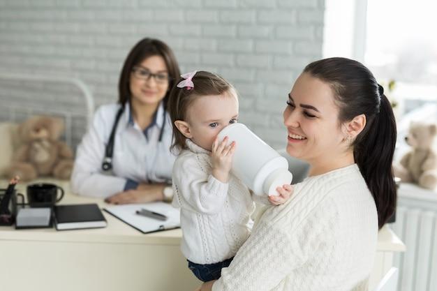 Porträt von mutter und kind beim arzttermin. kinderarzttreffen mit mutter und kind im krankenhaus.