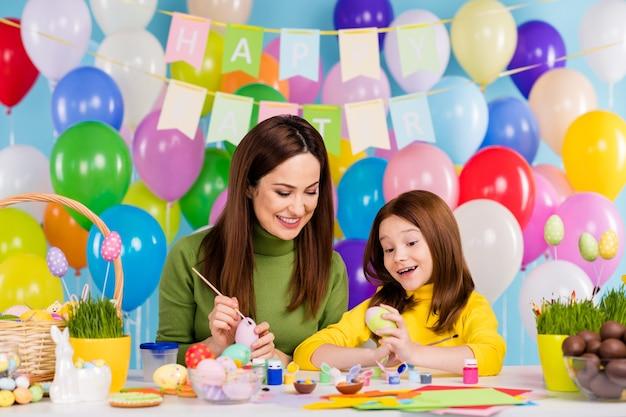 Porträt von netten attraktiven kreativen süßen süßen fröhlichen fröhlichen mädchenschwestern, die eier malen, die april festlichen tagesbrauch vorbereiten, der spaß meisterklasse hat