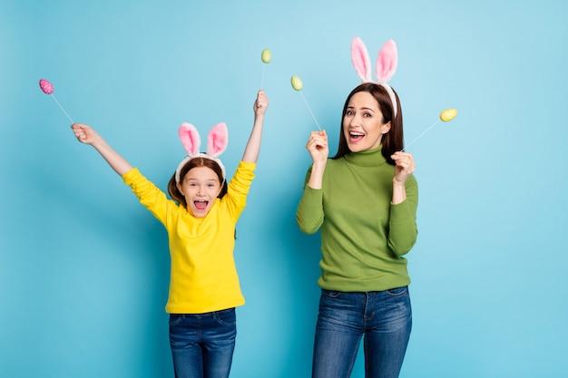 Porträt von netten attraktiven reizenden verspielten fröhlichen fröhlichen mädchen, die in den händen handgemachte eier auf stöcken halten, die spaß haben, der über hellem lebendigem glanz lebhafter blauer farbe isoliert wird