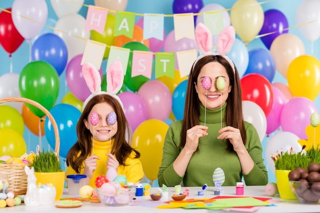 Porträt von netten attraktiven schönen reizenden lustigen fröhlichen fröhlichen fröhlichen mädchen, die spaß haben, die augen mit festlichen dekor-eiern zu bedecken, die täuschen, die festliche gute laune genießen