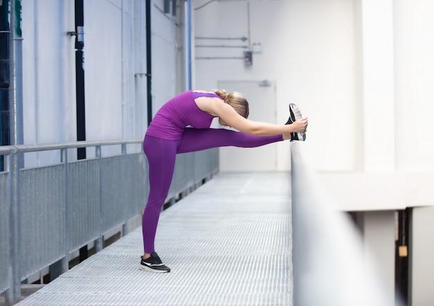 Porträt von netten frauen mit der sportkleidung, die yoga tut, werfen an im freien auf