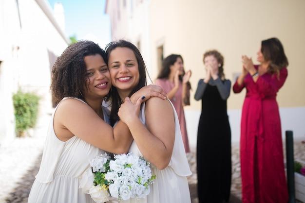 Porträt von netten lächelnden bräuten. zwei junge frauen umarmen sich. weibliche gäste lachen und applaudieren