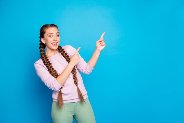 Porträt von niedlichen funky promoter mädchen punkt zeigefinger kopie raum auswählen vorschlagen verkaufsrabatte empfehlen promo tragen freizeitkleidung kleidung über hellem glanz farbe hintergrund isoliert
