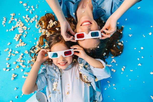 Porträt von oben niedliche mutter und tochter, die kopf an kopf lokalisiert auf blauem boden legen. tragen einer 3d-brille, langes brünettes haar, spaß mit popcorn, beste wochenenden, freizeit mit der familie