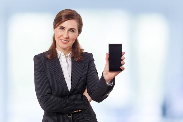 Porträt von ohren einer schönen geschäftsfrau 50 alt mit handy im büro.