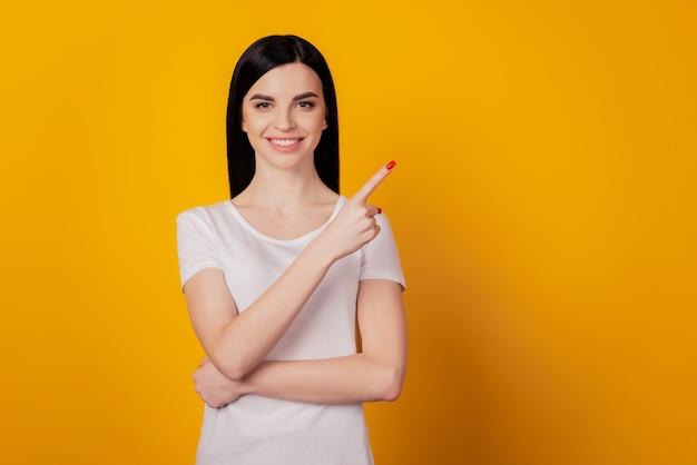 Porträt von positivem selbstbewusstem mädchen zeigen zeigefinger-exemplar für werbung, die auf gelbem hintergrund isoliert ist