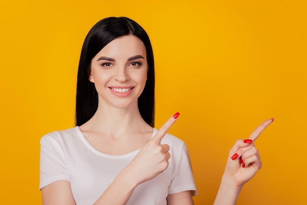 Porträt von positiven fröhlichen mädchen zeigen finger leeren raum werbung wahl isoliert auf gelbem hintergrund