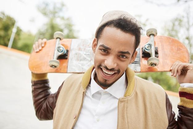 Porträt von positiven jungen teenagerübungen, die skateboard im freien reiten, hat glücklichen ausdruck