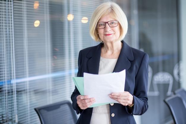 Porträt von positiven weiblichen manager mit dokumenten