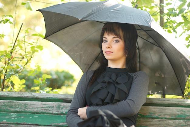 Porträt von schön mit regenschirm im park sitzend