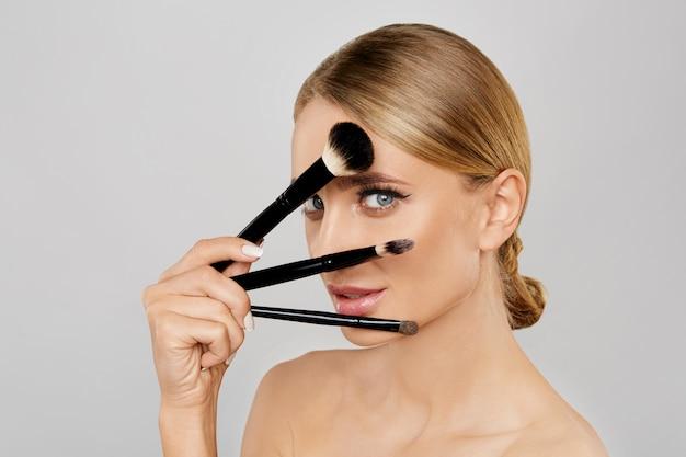 Porträt von schönen blondinen make-upbürsten halten. natürliches make-up.