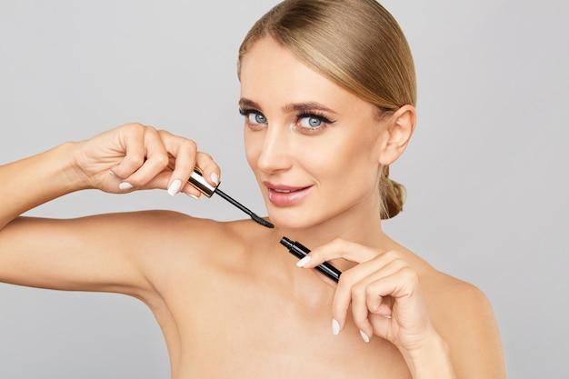 Porträt von schönen blondinen wimperntusche mit bürste anwendend. natürliches make-up. lange wimpern.