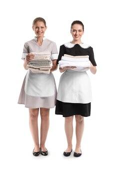 Porträt von schönen haushälterinnen mit sauberen handtüchern auf weißer oberfläche