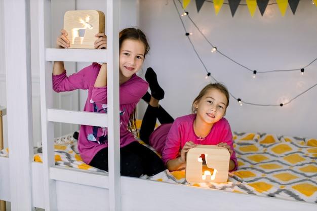 Porträt von schönen kindern, zwei kleinen hübschen mädchenschwestern, die mit hölzernen nachtlampen im stilvoll dekorierten etagenbett spielen. kinder, spielzeug, nachtlampen, abendzeitkonzept.