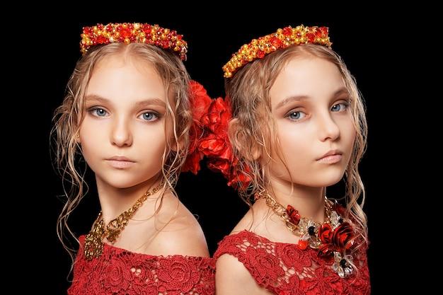 Porträt von schönen kleinen mädchen in roten kleidern auf schwarzem hintergrund