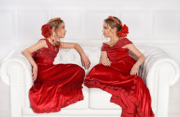 Porträt von schönen kleinen mädchen in roten kleidern im studio
