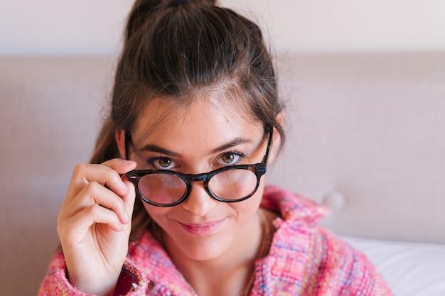 Porträt von schönen tragenden gläsern der jungen frau
