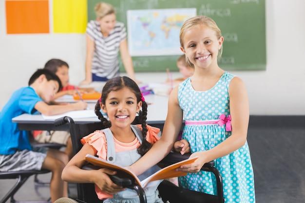 Porträt von schulkindern, die buch im klassenzimmer halten