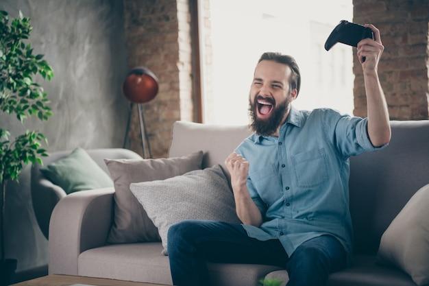 Porträt von seinem netten attraktiven fröhlichen fröhlichen überglücklichen verrückten brünetten kerl, der auf diwan sitzt, der online-spiel spielt, das spaß am innenraumhaus des industriellen dachbodens im modernen stil drinnen hat