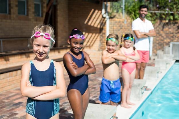 Porträt von selbstbewussten kleinen schwimmern mit männlichem ausbilder am pool