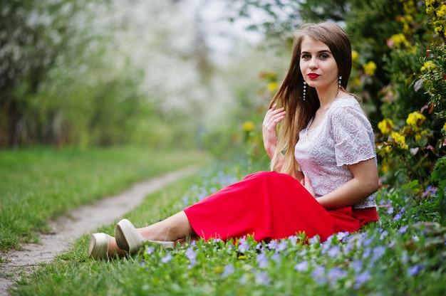Porträt von sitiing schönem mädchen mit den roten lippen am frühlingsblütengarten auf gras mit blumen, abnutzung auf rotem kleid und weißer bluse.