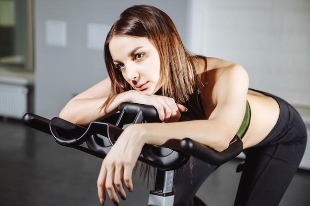 Porträt von spinnenden pedalen der erschöpften frau auf hometrainer.