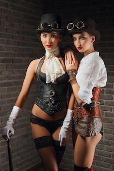 Porträt von steampunk-mädchen in hut mit schutzbrille und zuckerrohr in lederweste und strümpfen.