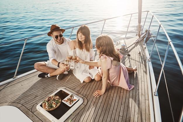 Porträt von stilvollen gutaussehenden europäern, die an bord der yacht zu mittag essen, wein trinken und die sommerzeit genießen. drei freunde leben in verschiedenen ländern und haben sich schließlich im urlaub kennengelernt