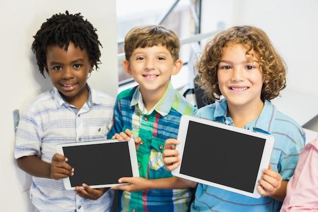 Porträt von studenten, die digitales tablett im klassenzimmer halten