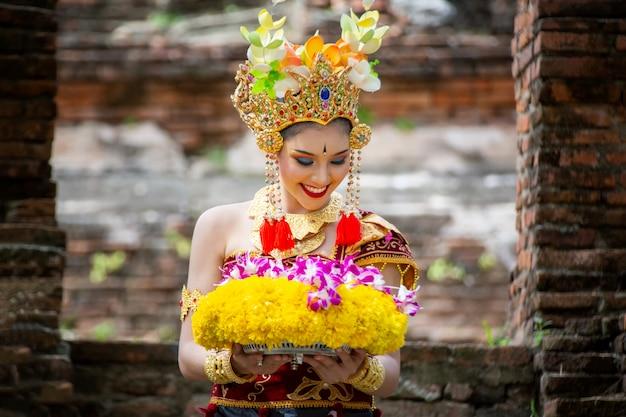 Porträt von tänzern eines balinesen hält opfergabe in der traditionellen kleidung am bali-tor